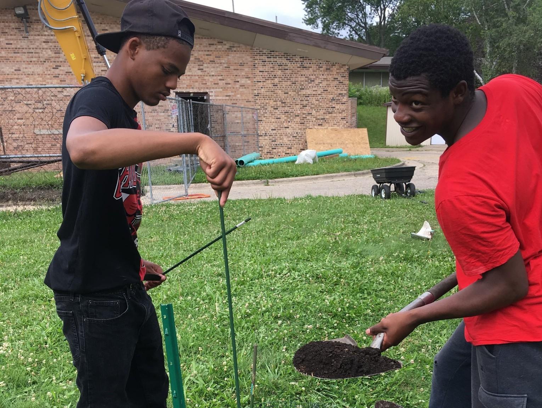 Antonio and Antonio stir the compost